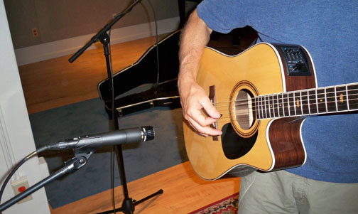 Moving the mic back to about 12 inches away from the sound hole evened out the response very effectively.