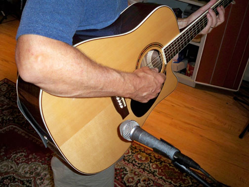 Here the SM-58 is placed just behind the bridge on the guitar's lower bout.